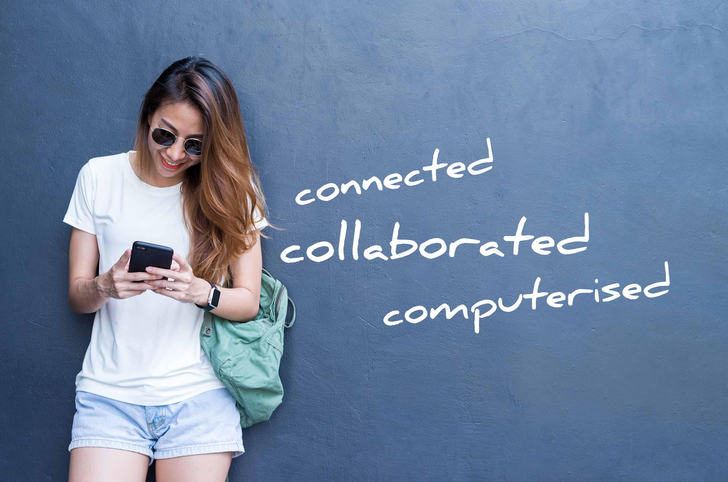 Jugendliches Mädchen steht an die Wand gelehnt mit dem Smartphone in der Hand