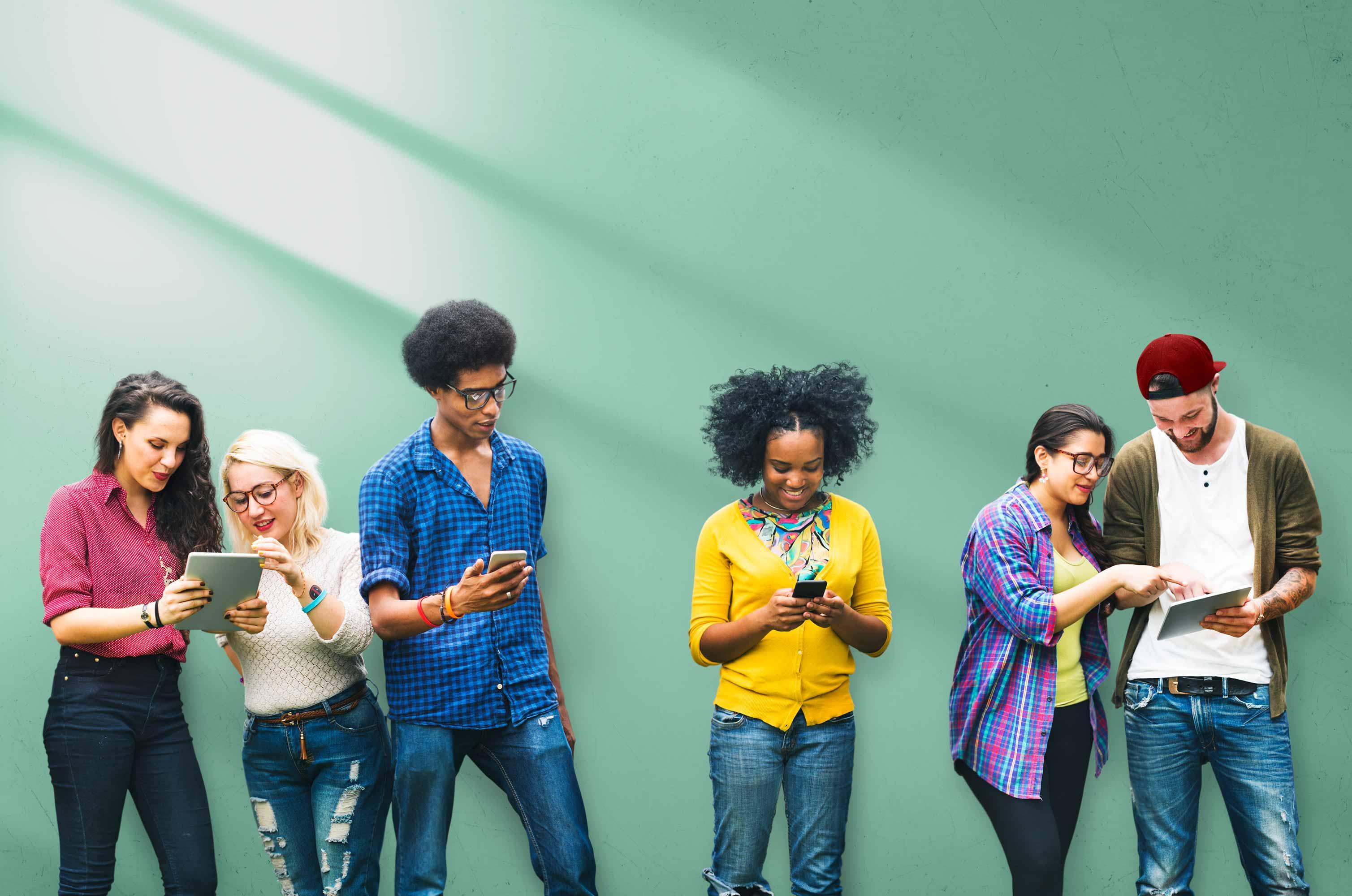 Verschieden aussehende Jugendliche stehen vor einer Wand und betrachten gemeinsam Inhalte auf mobilen Endgeräten
