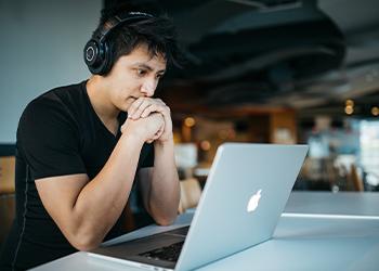 Mann sitzt konzentriert vor Laptop
