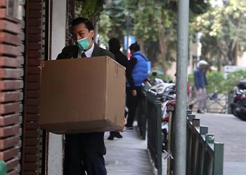 Mann mit großem Paket und Mundschutz